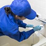 浴室の蛇口を清掃する作業着姿の女性